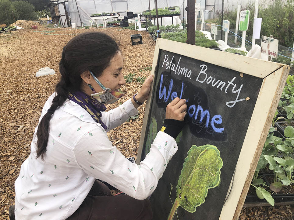 Farm Manager Reyna updates a chalkboard sign to welcome plant sale customers